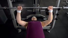 Hombre obeso que levanta encima del barbell, plan personal del entrenamiento del gimnasio, deseo de ser fuerte foto de archivo