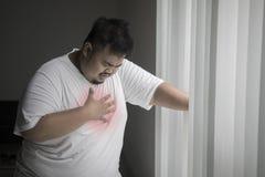 Hombre obeso que tiene un ataque del corazón cerca de la ventana imagen de archivo libre de regalías