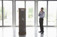 Hombre observando el paquete en oficina vacía Fotos de archivo libres de regalías