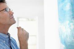Hombre observando la pintura en Art Gallery Fotos de archivo libres de regalías
