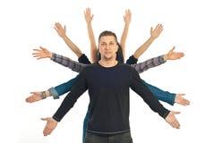 Hombre ocasional con diez manos alrededor de él Foto de archivo libre de regalías