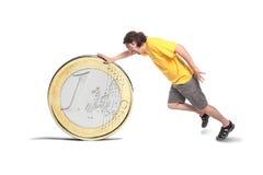 Hombre ocasional con una moneda euro grande Imagenes de archivo
