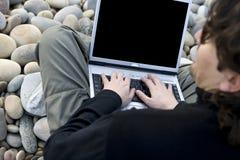 Hombre ocasional joven con el ordenador portátil en la playa Fotografía de archivo libre de regalías