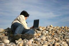 Hombre ocasional joven con la computadora portátil en la playa Imágenes de archivo libres de regalías