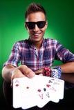 Hombre ocasional joven que muestra su mano de póker Foto de archivo