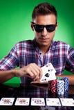 Hombre ocasional joven y su mano de póker fuerte foto de archivo