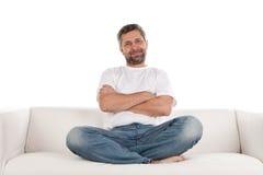 Hombre ocasional que se sienta en el sofá Imágenes de archivo libres de regalías