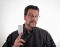 hombre ocasional que sostiene la tarjeta de visita en blanco Imagen de archivo libre de regalías
