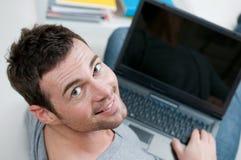 Hombre ocasional sonriente que trabaja en la computadora portátil Fotografía de archivo