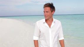 Hombre ocasional vestido que camina a lo largo de la playa metrajes