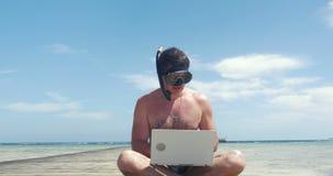 Hombre ocupado en tubo respirador y máscara con el ordenador portátil almacen de metraje de vídeo