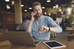 Hombre ocupado joven que tiene llamada de teléfono en café Fotos de archivo libres de regalías