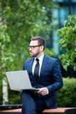 Hombre ocupado que se sienta en el banco que sostiene el ordenador portátil imagenes de archivo