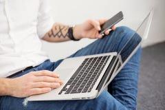 Hombre ocupado que trabaja con el ordenador y que usa el teléfono móvil Foto de archivo libre de regalías