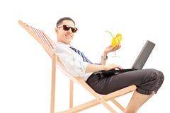 Hombre ocupado sonriente con el ordenador portátil que se sienta en una silla de playa y un holdin Imagen de archivo libre de regalías