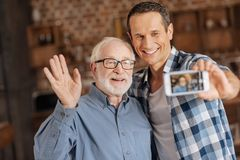 Hombre optimista que toma imágenes con su padre mayor imagen de archivo libre de regalías