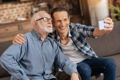 Hombre optimista que toma un selfie con su padre mayor Fotografía de archivo libre de regalías