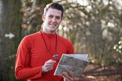 Hombre Orienteering en arbolados con el mapa y el compás Imagenes de archivo