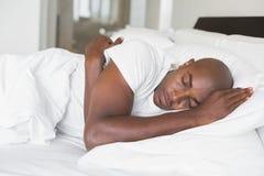 Hombre pacífico que duerme en cama fotografía de archivo libre de regalías
