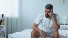 Hombre parado triste que se sienta en el dormitorio, pensando en los planes para el futuro presionado metrajes