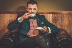 Hombre pasado de moda confiado que se sienta en silla de cuero cómoda con la taza de café en interior de madera en la peluquería  Foto de archivo