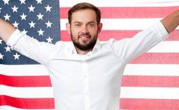 Hombre patriótico sonriente que sostiene la bandera de Estados Unidos Los E.E.U.U. celebran el 4 de julio Foto de archivo libre de regalías