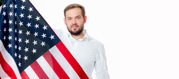 Hombre patriótico sonriente que sostiene la bandera de Estados Unidos Los E.E.U.U. celebran el 4 de julio Fotografía de archivo libre de regalías