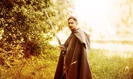 Hombre peligroso con la espada medieval Fotos de archivo libres de regalías