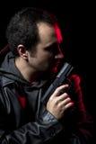 Hombre peligroso con un arma y una chaqueta de cuero negra Imagen de archivo