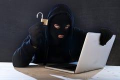 Hombre peligroso del pirata informático con el ordenador y la cerradura que cortan el sistema en concepto cibernético del crimen Fotografía de archivo libre de regalías