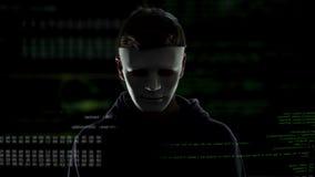 Hombre peligroso en la máscara blanca en el fondo de los códigos y de los números, cortando concepto metrajes