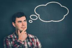 Hombre pensativo con la burbuja del pensamiento en la pizarra Fotos de archivo libres de regalías