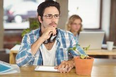 Hombre pensativo con la mano en la barbilla que se sienta en oficina Imagen de archivo
