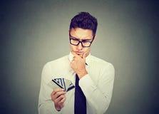 Hombre pensativo con muchas diversas tarjetas del descuento de la lealtad del crédito fotografía de archivo