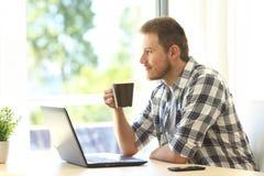 Hombre pensativo con un ordenador portátil Fotos de archivo libres de regalías