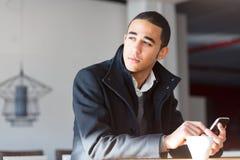 Hombre pensativo en capa con el teléfono celular Foto de archivo libre de regalías
