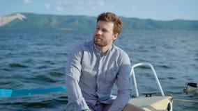 Hombre pensativo en el yate que sienta y que disfruta de vistas del mar metrajes