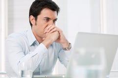 Hombre pensativo en la computadora portátil Imagenes de archivo