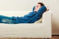 Hombre pensativo joven que se relaja en el sofá Foto de archivo libre de regalías