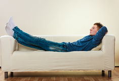 Hombre pensativo joven que se relaja en el sofá Foto de archivo