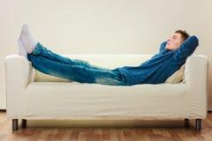 Hombre pensativo joven que se relaja en el sofá Imagenes de archivo