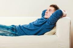 Hombre pensativo joven que se relaja en el sofá Fotografía de archivo libre de regalías
