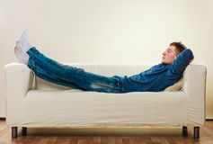 Hombre pensativo joven que se relaja en el sofá Imagen de archivo