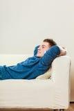 Hombre pensativo joven que se relaja en el sofá Imagen de archivo libre de regalías