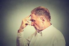 Hombre pensativo mayor aislado en fondo gris de la pared Imagen de archivo
