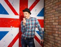 Hombre pensativo que fuma usando el tubo en bandera BRITÁNICA delantera Imagenes de archivo