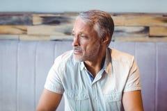 Hombre pensativo que mira lejos en cafetería Fotografía de archivo libre de regalías