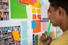 Hombre pensativo que mira notas pegajosas en oficina Foto de archivo libre de regalías