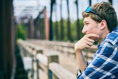 Hombre pensativo que se coloca en el puente y el pensamiento Fotos de archivo
