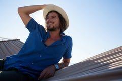 Hombre pensativo que se relaja en la hamaca en la playa Imagen de archivo libre de regalías